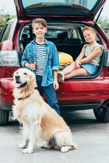 children and dog with packed car | Island Real Estate
