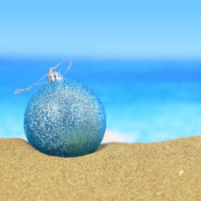 blue holiday ornament in the sand