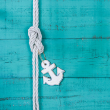 white rope know and small anchor on wood plank background