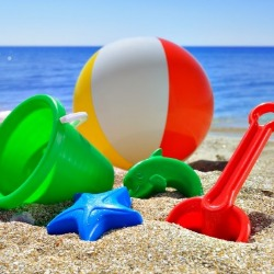beach ball, shovel, and toys on the beach | Island Real Estate