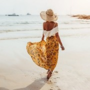 woman walking on the beach in a long skirt | Island Real Estate