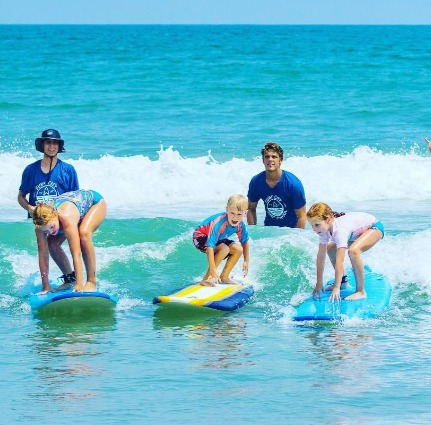 students surfing at Surf City Surf School | Island Real Estate
