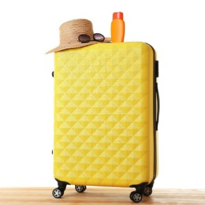 yellow four wheeled hard shell suitcase | Island Real Estate