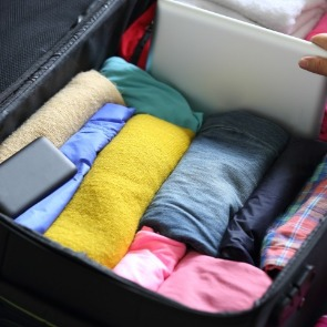 clothing rolled up in a suitcase | Island Real Estate