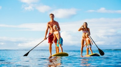 family paddle boarding on topsail beach | Island Real Estate